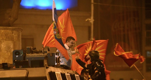 A police officer tries to grab a protester waving former Macedonian and Russian flags atop an armored police vehicle during protests in front of Parliament, Skopje, June 17.