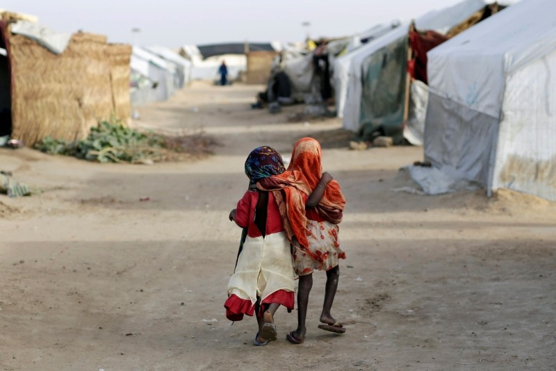 Ami and Ashbu, both three years old, walk arm in arm in the Zafaye refugee camp, some 15 kilometers from downtown N'djamena, Chad, March 11, 2015. (AP Photo)