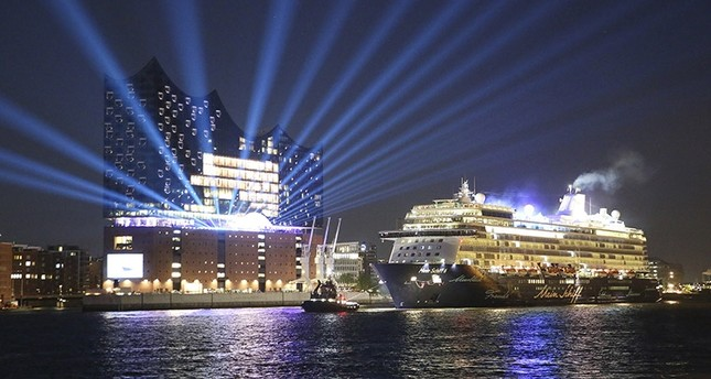 In this May 31, 2017 photo Cruise ship Mein Schiff 6 passes the Elbphilharmonie concert hall during a test run  in Hamburg, Germany. (AP Photo)