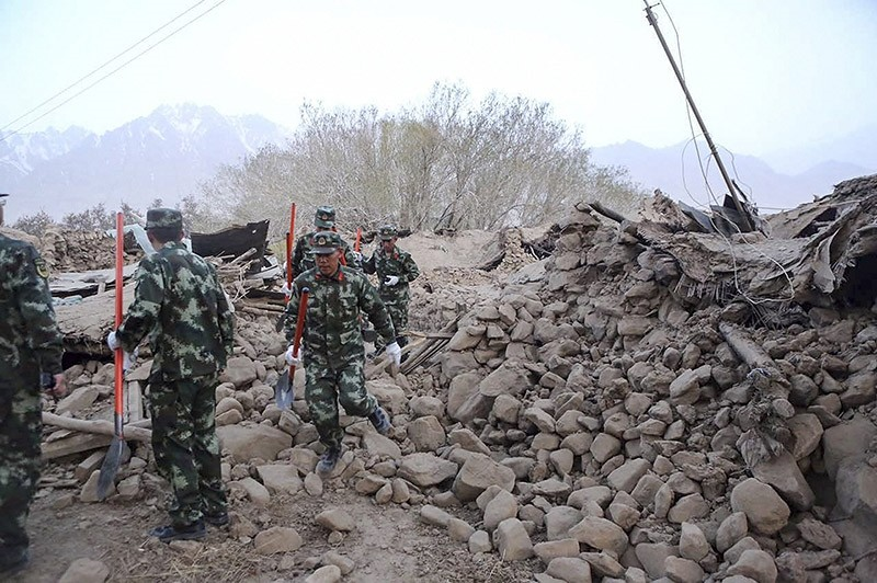In this photo released by Xinhua News Agency, soldiers walk past damaged houses following an earthquake in Kuzigun Village in Taxkorgan County, northwest China's Xinjiang Uygur Autonomous Region, Thursday, May 11, 2017. (AP Photo)