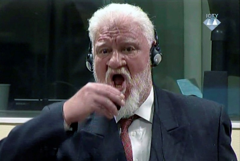 In this ICTY file photo dated Wednesday, Nov. 29, 2017, Slobodan Praljak drinks from a bottle after proclaiming his innocence shortly after hearing an appeals judge confirmed his 20-year sentence for crimes during the 1992-95 Bosnian war. (AP Photo)