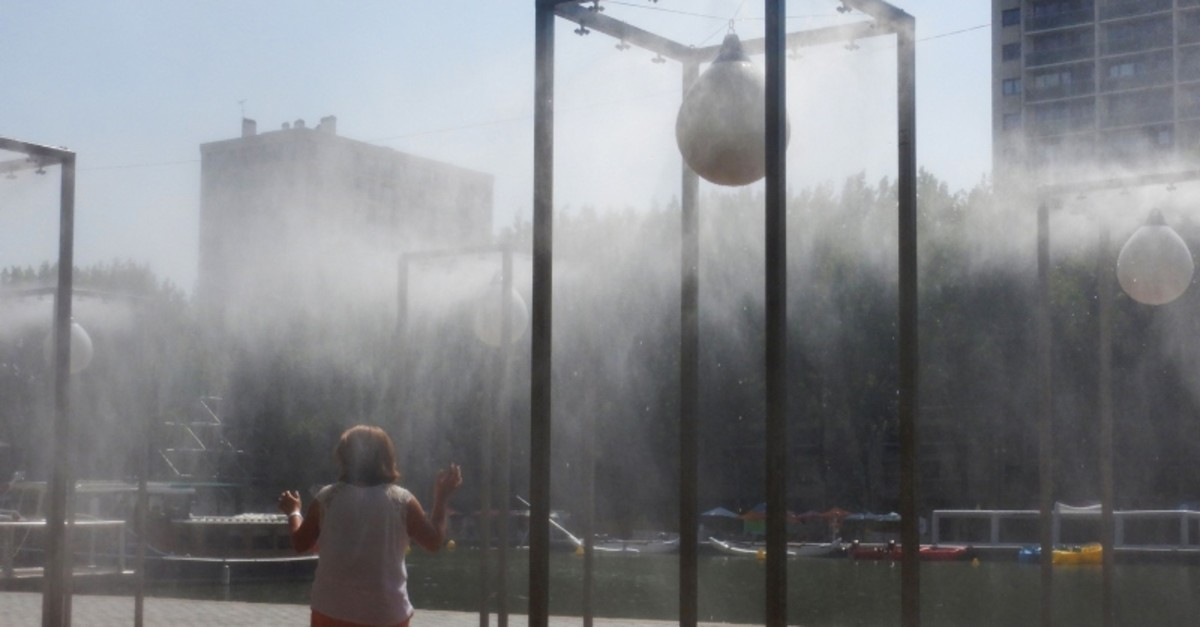 In this file photograph taken on July 24, 2019, a woman refreshes herself under water atomizers during a heatwave, at The Bassin de la Villette in Paris. - French scientists warned on September 17, 2019 (AFP Photo)