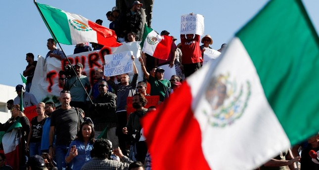 Demonstrators holding a placard that read, Not to the invasion and waving Mexican flags, attend a protest against migrants who are part of a caravan traveling en route to the United States, in Tijuana, Mexico November 18, 2018. (Reuters Photo)