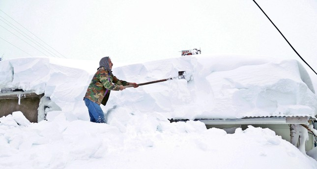 A man shovels snow from the roof of a house in the eastern city of Elazığ, Jan. 16, 2019.