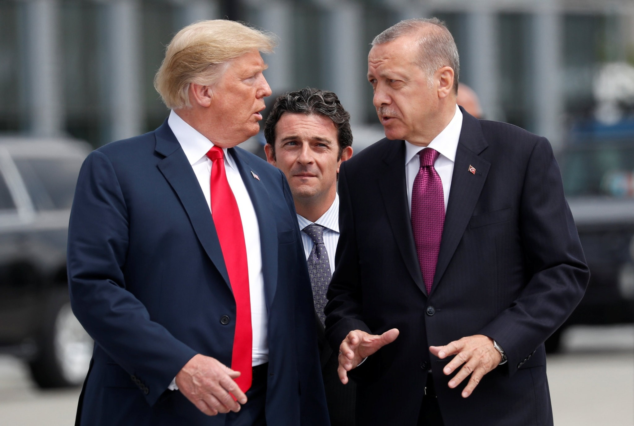U.S. President Donald Trump (L) and President Recep Tayyip Erdou011fan gesture as they talk at the start of the NATO summit in Brussels, Belgium, July 11.