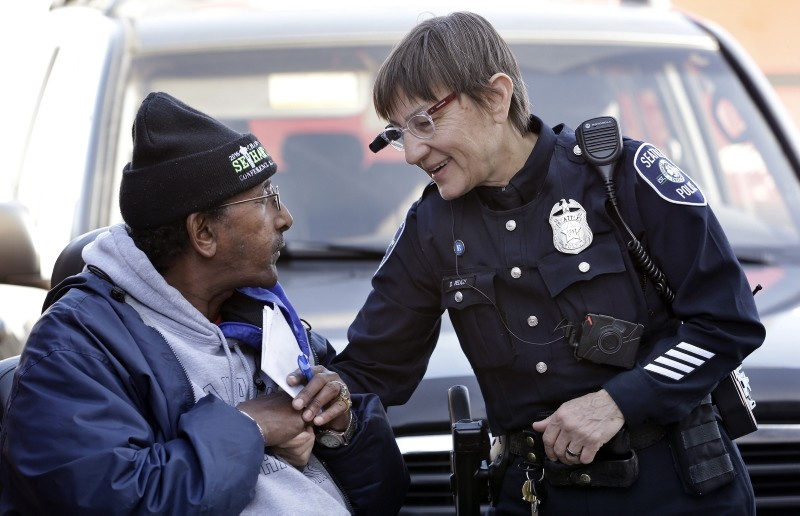 In this March 12, 2015, file photo, Seattle police officer Debra Pelich, right, wears a video camera on her eyeglasses as she talks with Alex Legesse before a small community gathering in Seattle. (AP Photo)