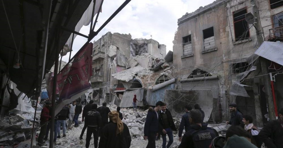 People walk past destruction caused by regime airstrikes in the town of Ariha, Idlib, Jan.15, 2020. (AP PHOTO)