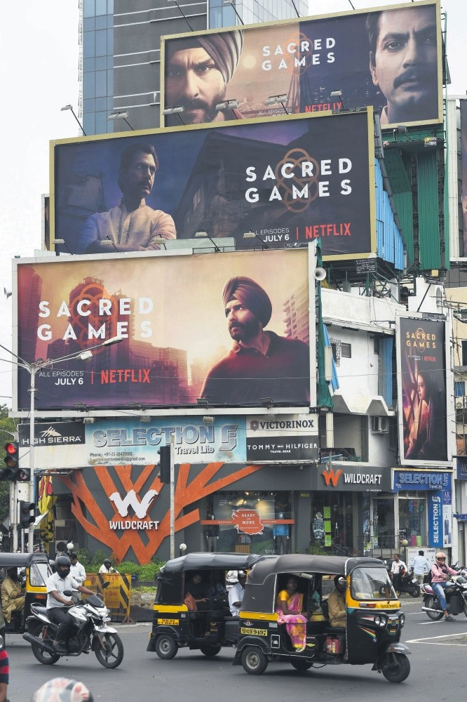 Indian commuters travel past large billboards for u2018Sacred Games,' the upcoming Indian series on Netflix, in Mumbai.