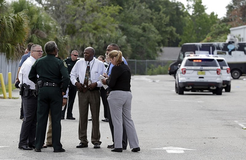 Authorities confer near the scene of a shooting where they said there were multiple fatalities in an industrial area near Orlando, Fla., Monday, June 5, 2017. (AP Photo)