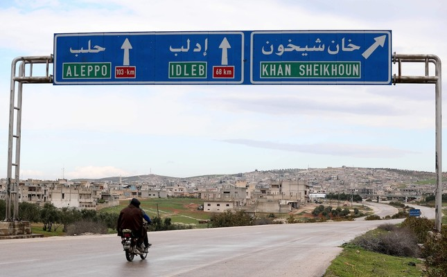 Two Syrian men drive past road signs in Khan Sheikhun, July 28, 2019.