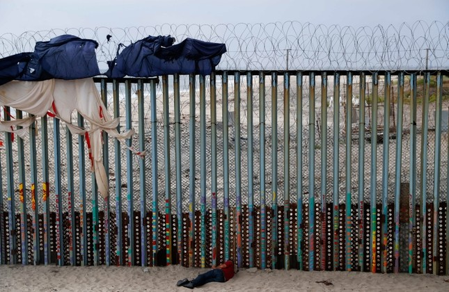 A man sleeps next to the U.S. border wall topped with razor wire in Tijuana, Mexico, Sunday, June 9, 2019. (AP Photo)