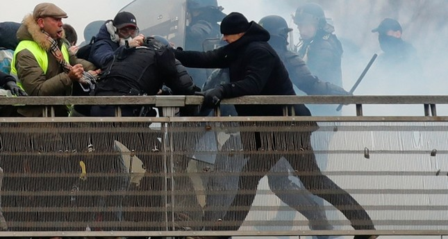 Former French boxer Christophe Dettinger, the one with the black beaine, seen during clashes with Gendarmerie as part of a demonstration by the yellow vests on the passerelle Leopold-Sedar-Senghor bridge in Paris, France, January 5, 2019. (Reuters)