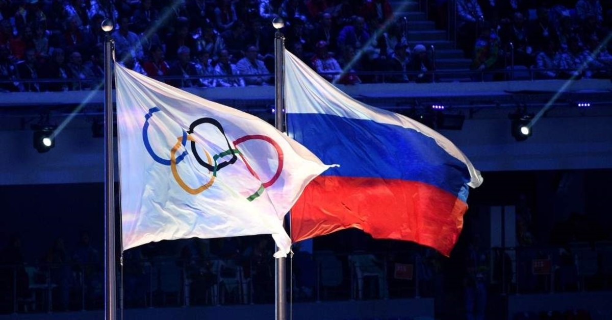 The Olympic flag and the Russian flag flying in Sochi, Feb. 23, 2014. (AFP Photo)