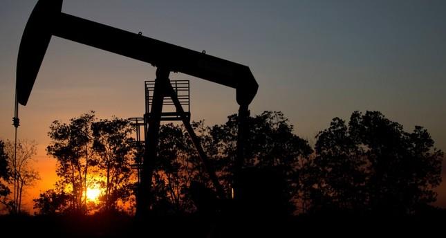 In this Feb. 19, 2015 photo, the sun sets behind an oil well in a field near El Tigre, Venezuela. AP Photo