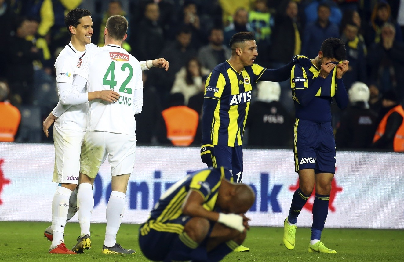 Alper Potuk wipes his tears with his jersey while Nabil Dirar buries his head between his legs at the end of Konyaspor match in Istanbul Feb. 17, 2019 while Konyaspor players Petar Filipovic (left) and Deni Milosevic (second left) cheer.