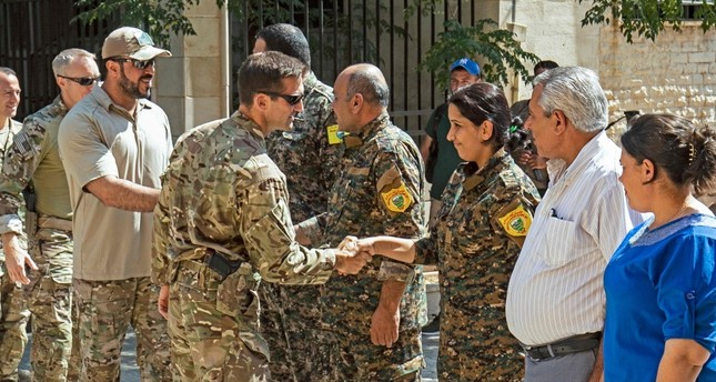 Members of the U.S.-led coalition forces shake hands with People's Protection Unit YPG terrorists in Tal Abyad, Sept. 15, 2019.