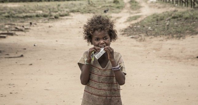 A girl eats a food supplement distributed during a malnutrition screening session organised by a nongovernmental organization and the World Food Programme (WFP) in the municipality of Ifotaka.