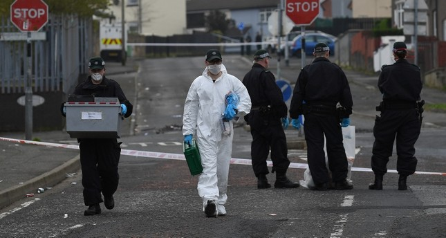 Police officers carry a box of evidence as they leave the scene where the 29-year-old journalist Lyra McKee was shot dead, in Londonderry, Northern Ireland April 19, 2019. (Reuters Photo)