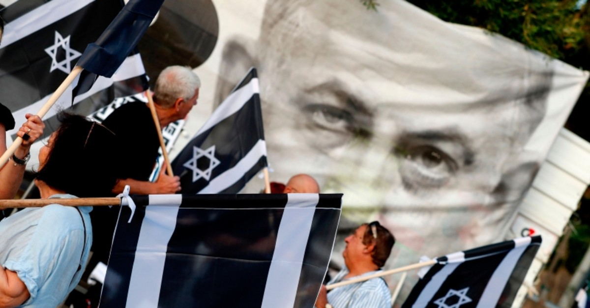 Israeli oposition parties' supporters hold flags as they attend a rally against Prime Minister Benjamin Netanyahu on May 25, 2019 in the coastal city of Tel Aviv.