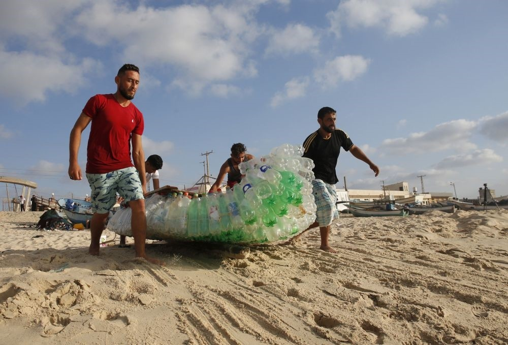 Palestinian fisherman Mouad Abu Zeid (R) and his friends carry his boat that he made from 700 empty plastic bottles on a beach in Rafah, Gaza.