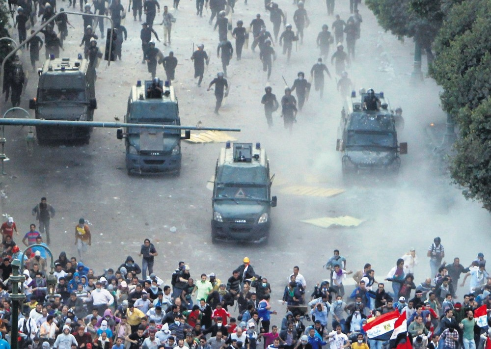 Protesters run from riot police during a demonstration against the junta regime in their country, at Tahrir square, Cairo, Nov. 23, 2012.