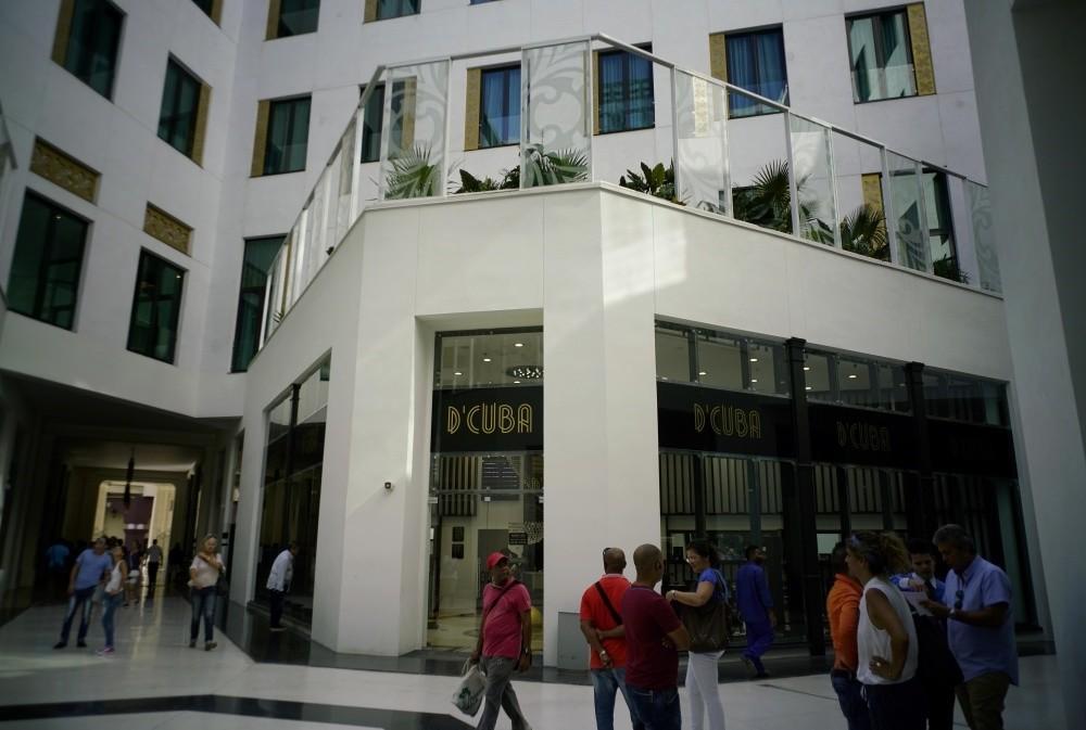 People look at luxury storefronts at the Manzana de Gomez Kempinski five-star hotel in Havana, Cuba.