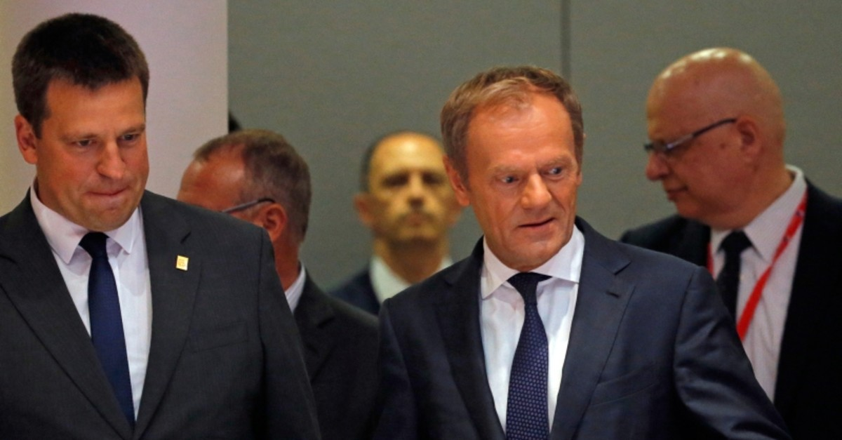 European Council President Donald Tusk, center, and Estonian Prime Minister Juri Ratas, left, arrive for a round table meeting at an EU summit in Brussels, Sunday, June 30, 2019. (AP Photo)