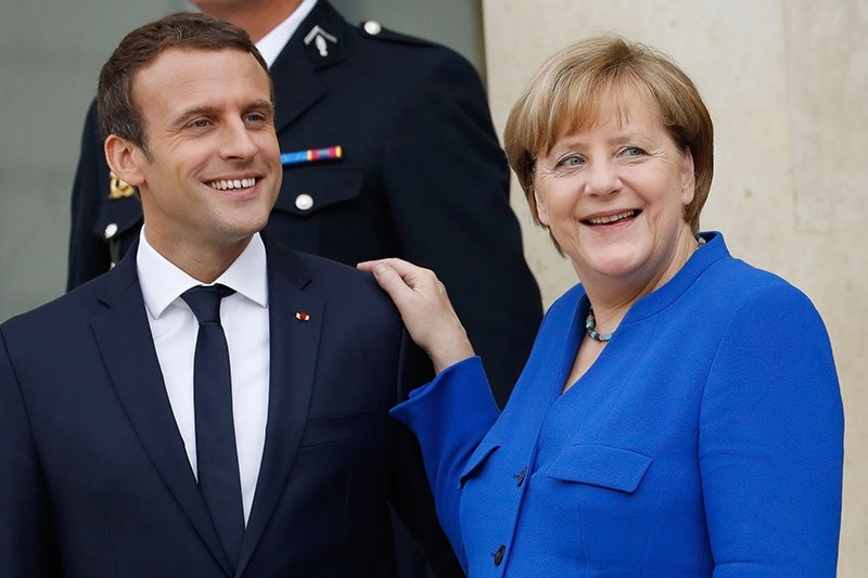 German Chancellor Angela Merkel (R) and French President Emmanuel Macron leave the Elysee Palace in Paris on July 13, 2017, after an annual Franco-German Summit. (AFP Photo)
