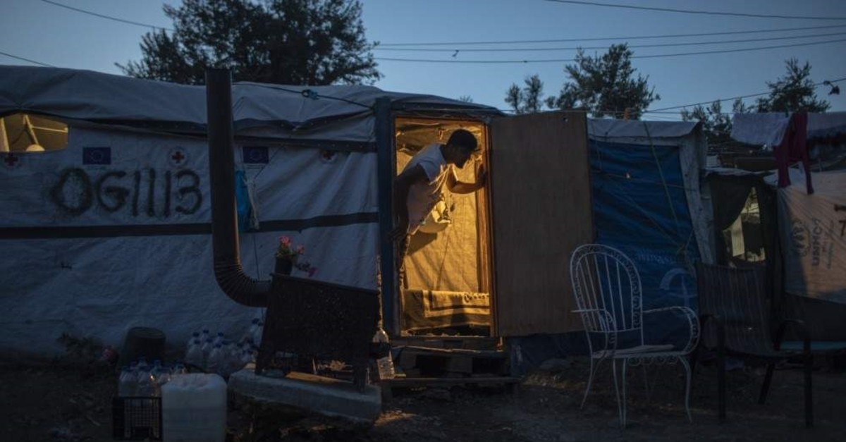 In this Thursday Oct. 3, 2019 photo, an Afghan man looks out of his tent at a makeshift refugee and migrant camp on the fringes of the overcrowded Moria camp on the Greek island of Lesbos. (AP Photo)