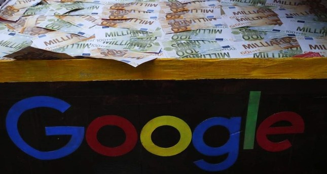 A trunk full of fake bank notes is displayed as activists from anti-globalization organization Attac stage a protest at Google's Paris headquarters to criticize the company's tax evasion policies, in Paris, Jan. 31, 2019. AP Photo
