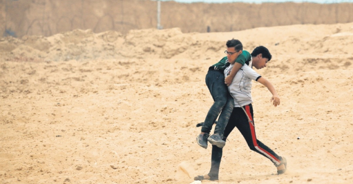 A Palestinian protester carries an injured young boy during border protests, Gaza, Oct. 1, 2018.