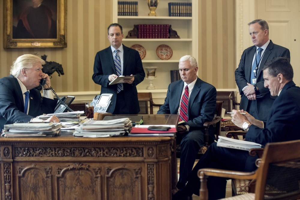Trump (L), speaking on the phone with Putin, in Oval Office at the White House in Washington, accompanied by, from left-to-right, Chief of Staff Priebus, VP Pence, White House press secretary Spicer and then-National Security Adviser Flynn, Jan. 28.