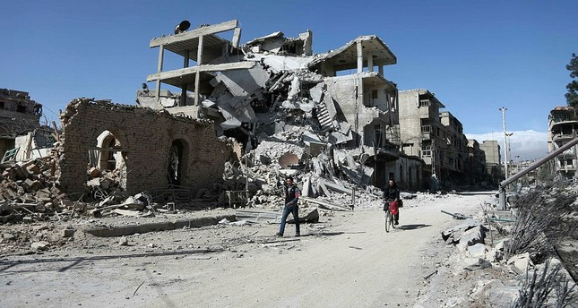 Syrians walk past destroyed buildings in the rebel-held town of Hamouria, in the besieged Eastern Ghouta region on the outskirts of the capital Damascus, on March 9, 2018. (AFP Photo)