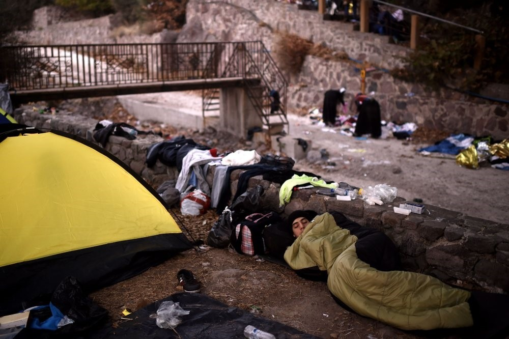 A man sleeps near a tent on the street along with other refugees and migrants after arriving on the Greek island of Lesbos by crossing the Aegean Sea from Turkey, Oct. 7, 2015.