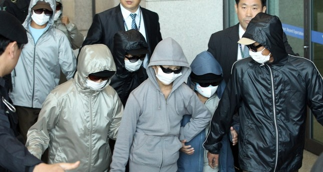 A group of nine North Korean defectors who have been under protective custody in Japan for nearly three weeks arrives at Incheon airport, west of Seoul, on 04 October 2011. (EPA Photo)
