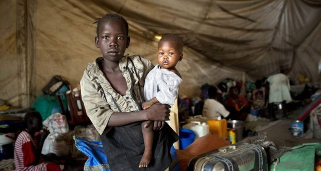 A young girl, displaced by fighting, holding her baby brother in a tent on the UN base in South Sudan, 30 March 2014. (EPA Photo)