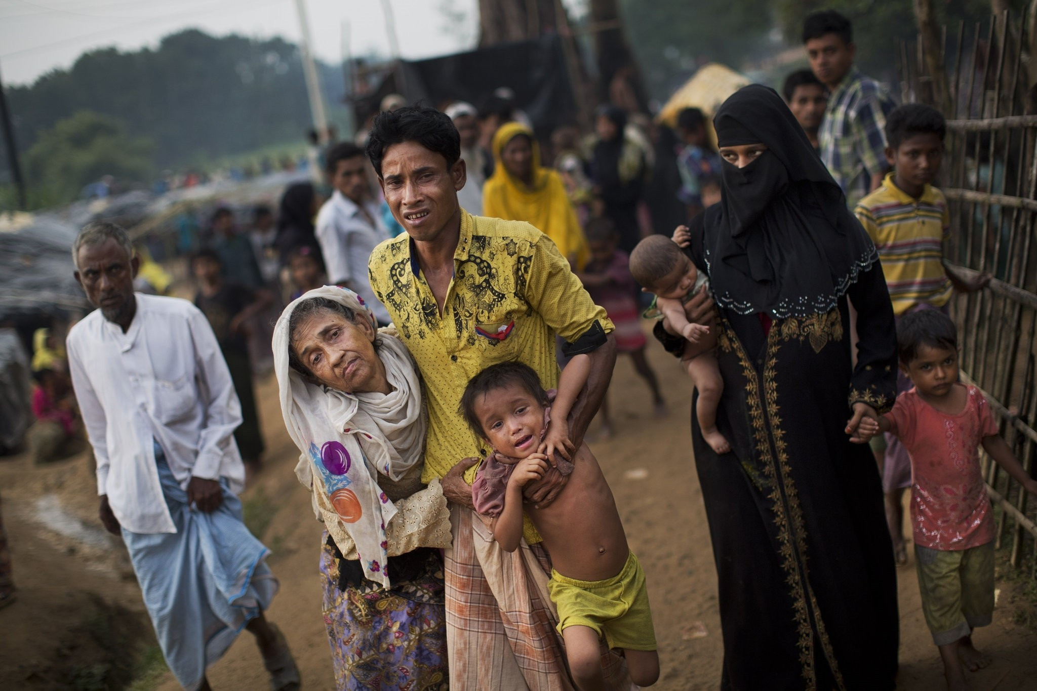 A Rohingya helps an elderly family member and a child as they arrive at Kutupalong refugee camp after crossing from Myanmmar to the Bangladesh side of the border. (AP Photo)