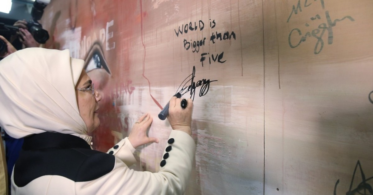 Emine Erdou011fan writes ,World Is Bigger Than Five, on a wall where participants sign at an event on the sidelines of the forum.