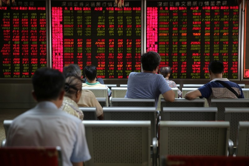 Chinese investors watch an electronic board showing the stock index and prices at a securities brokerage house in Beijing, China, June 26, 2018. (EPA Photo)