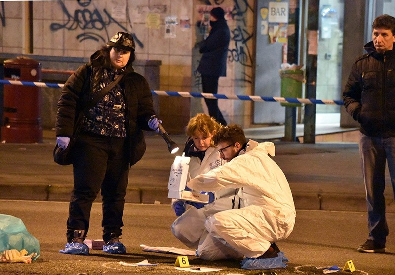Italian forensic police inspect an area after a shootout between police and a man near a train station in Milan's Sesto San Giovanni neighborhood, Italy, early Friday, Dec. 23, 2016. (AP Photo)