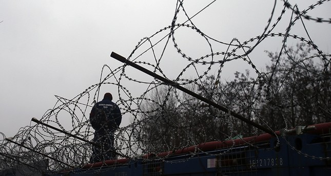 A Hungarian police officer stands guard at Serbia's border with Hungary near a makeshift camp for migrants in Horgos, Serbia, Wednesday, Feb. 8, 2017 (AP Photo)