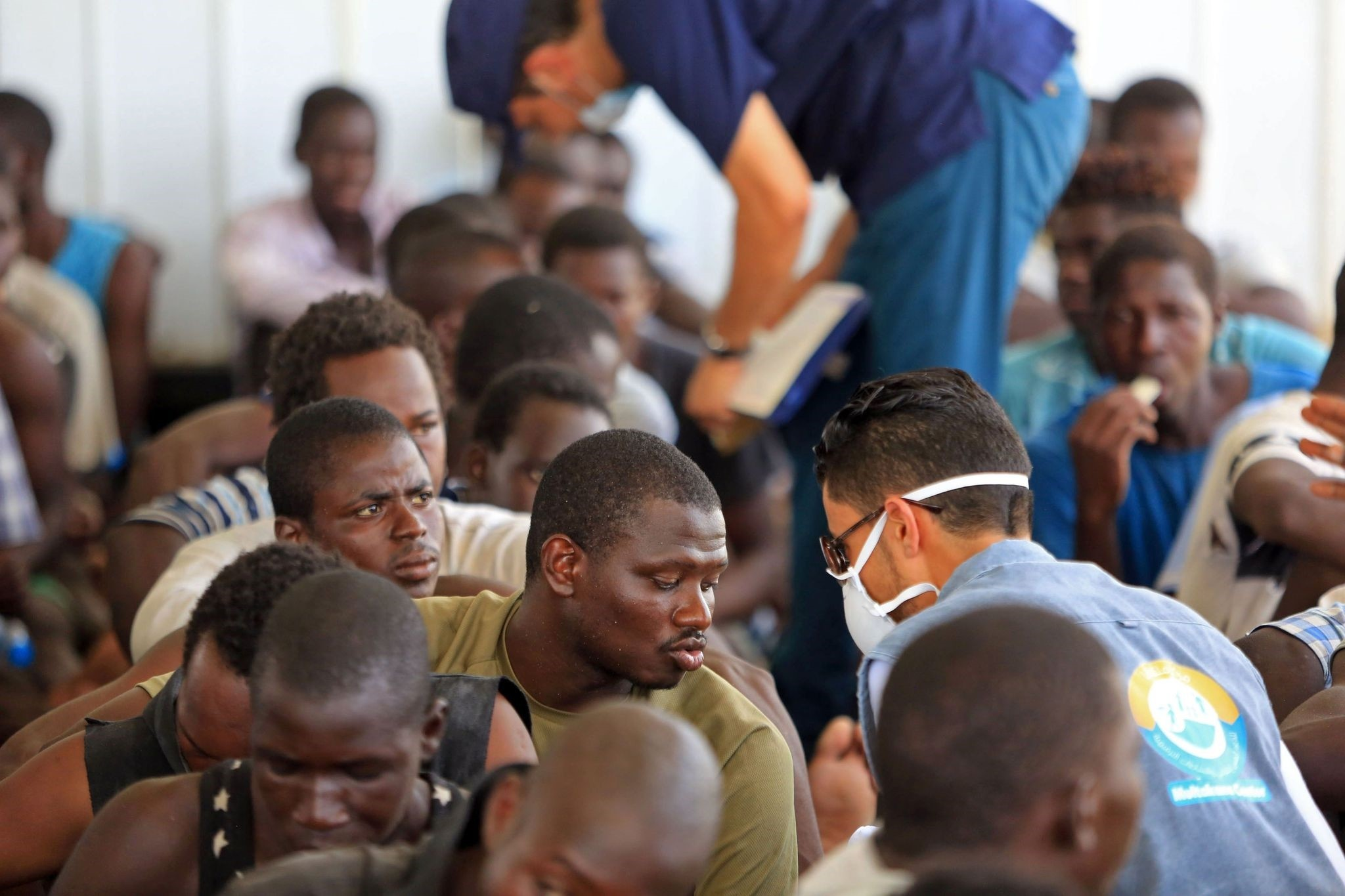 Aid workers talk with migrants from Africa, at a naval base in Tripoli after they were rescued by Libyan coastguards in the Mediterranean Sea off the Libyan coast, on July 24, 2017. (AFP Photo)
