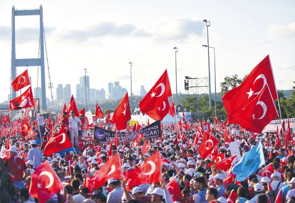 People wave Turkish national flags as they stand near the July 15 Martyrs Bridge in Istanbul on July 15, 2017. Turkey has marked almost two years since the defeat of the coup attempt.