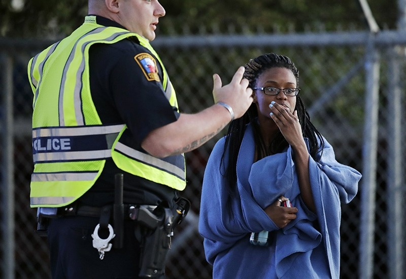 An employee wrapped in a blanket talks to a police officer after she was evacuated at a FedEx distribution center where a package exploded, Tuesday, March 20, 2018, in Schertz, Texas. (AP Photo)