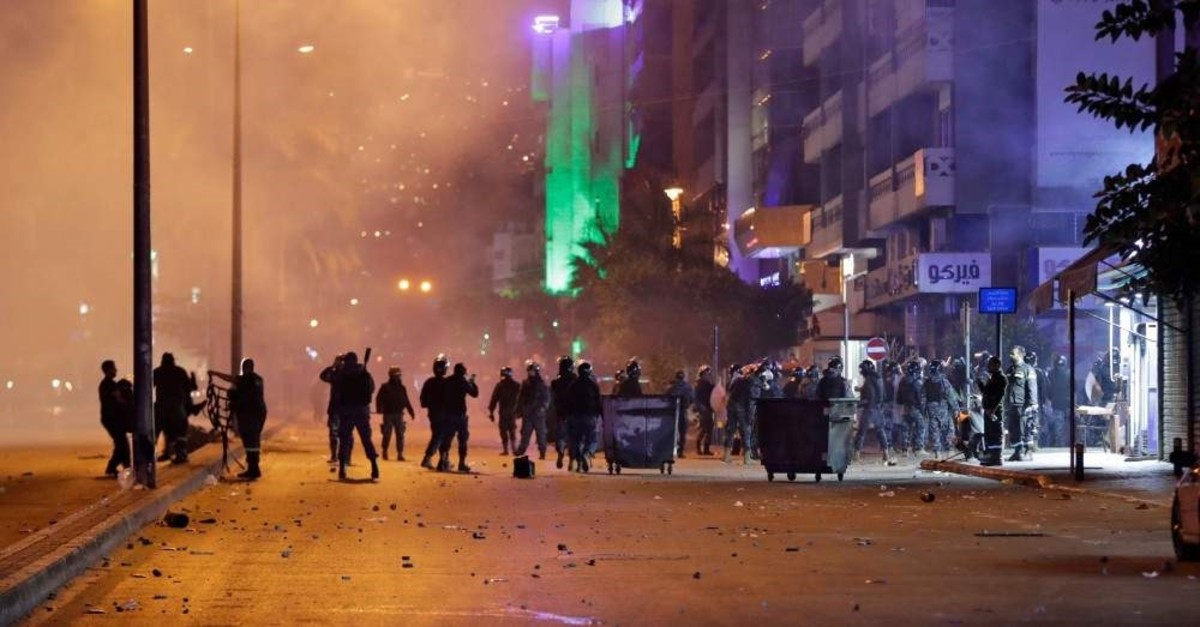 Lebanese anti-government protesters gather during clashes with riot police following a demonstration outside the police barracks, Beirut, Jan. 15, 2020. (AFP Photo)