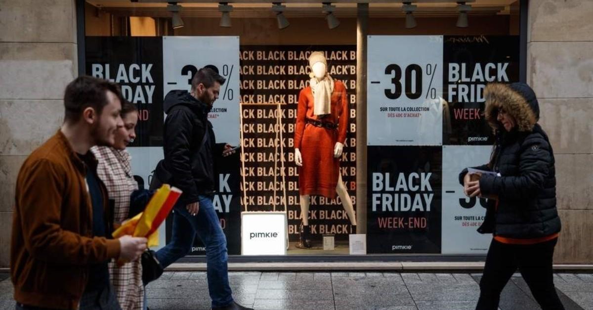 Pedestrians walk past a shop announcing Black Friday sales in Caen, France, Nov. 27, 2019. (AFP)