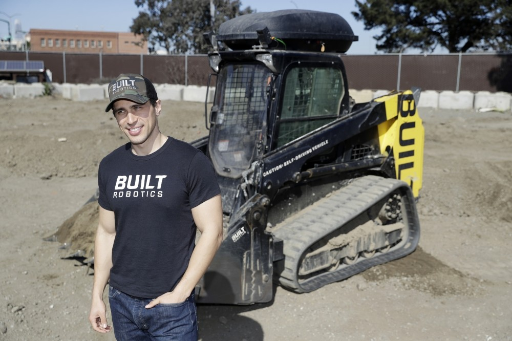 Built Robotics CEO Noah Ready-Campbell poses for a picture in front of the company's autonomous track loader in San Francisco.