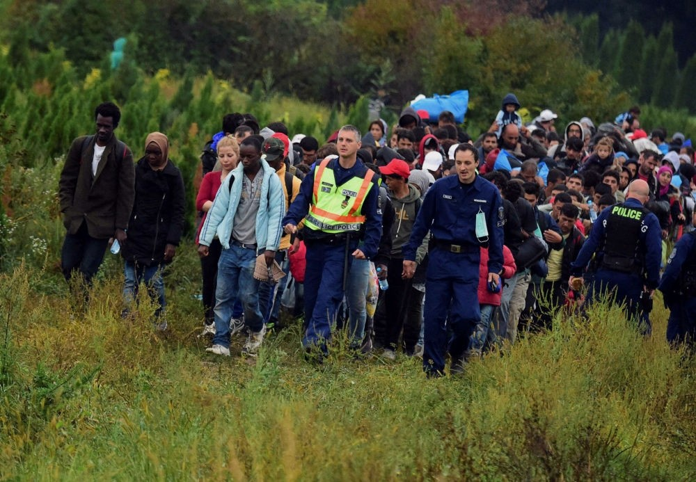 Police escort migrants after they crossed the border near the village of Zakany in Hungary to continue their trip to Gemany.
