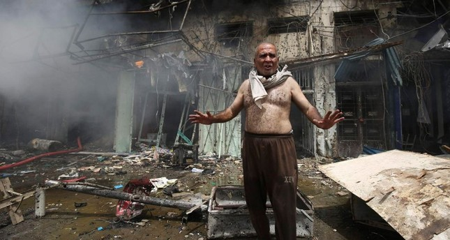 An Iraqi man shouts after a bomb destroyed his home in Baghdad.