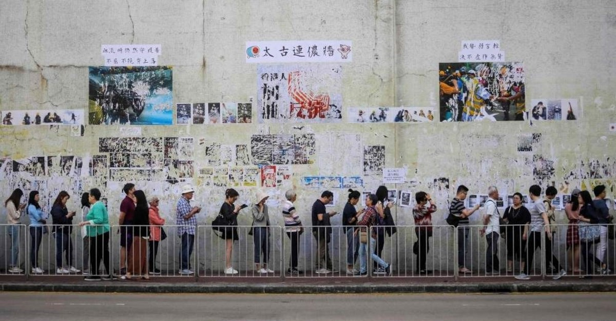 People queue to cast their vote in front of a ,Lennon Wall, adorned with tattered posters in support of the ongoing protests, during the district council elections in Tai Koo in  Hong Kong on November 24, 2019. (AFP Photo)